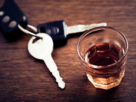 Set of car keys laying next to a whiskey highball