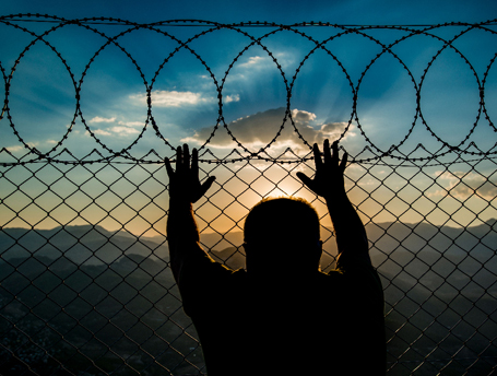 Prisoner watches sunset from behind a barbed wire prison fence